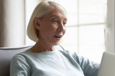 Head shot close up surprised older woman received email with unbelievable news, sitting with computer at home. Excited mature lady looking at device screen, getting unexpected shopping offer deal. Stock Photo
