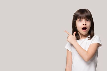 Stunned little girl isolated on grey studio background point at blank copy space in photostudio, surprised small child show at amazing unbelievable sale offer or deal, free advertising place