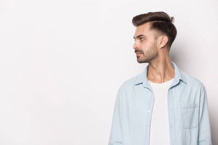 Serious millennial caucasian man in shirt stand in side profile view isolated on grey studio background look at blank copy space, focused male peek at advertising offer, deal, consider promotion Banco de Imagens