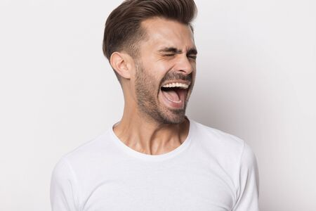 Angry caucasian young man in white t-shirt isolated on grey studio background scream shout displeased with offer, furious bearded millennial male yell loudly displeased with news or suggestion