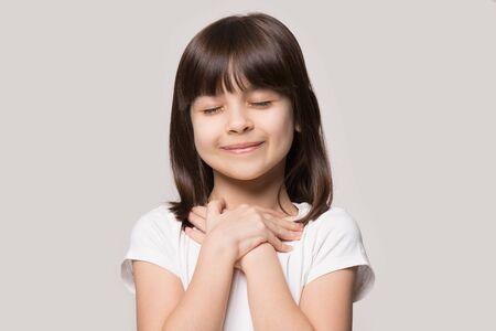 Cerca de linda niña feliz aislada sobre fondo gris de estudio tomarse de las manos en el pecho del corazón sentirse agradecido, niño sonriente con los ojos cerrados orar agradeciendo a Dios altos poderes, concepto de fe Foto de archivo