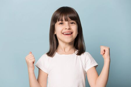 Headshot portrait of overjoyed cute little girl isolated on blue studio background look at camera feel euphoric, happy small kid excited pleased with online win, personal success school achievement