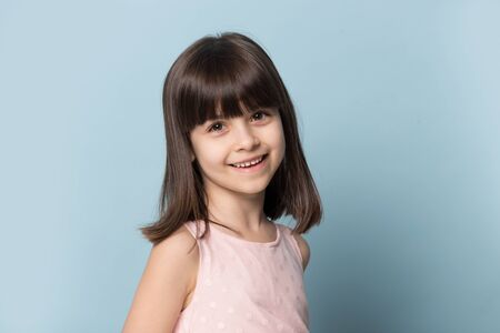 Close up headshot portrait of smiling cute little brunette girl isolated on blue studio background look at camera, happy small preschooler kid model posing shooting or casting in photostudio Banco de Imagens