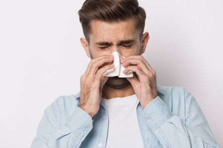 Sick young caucasian man isolated on grey studio background use handkerchief blow nose suffering from influenza, unhealthy ill guy with paper tissue having runny nose, catch cold, need medication