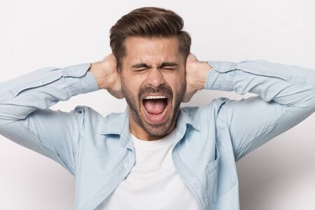 Close up of furious caucasian young man isolated on grey studio background close ears scream bothered by loud noise, angry mad male shout yell lose patience ignoring avoiding noisy unbearable sound