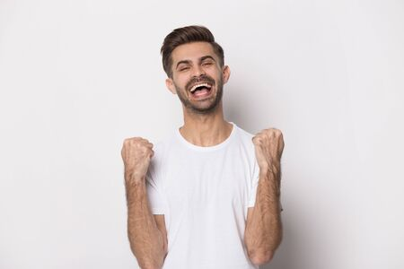 Overjoyed caucasian young man in white t-shirt isolated on grey studio background pleased with win or success, excited happy millennial guy scream yell triumph feel euphoric with good unexpected news 스톡 콘텐츠