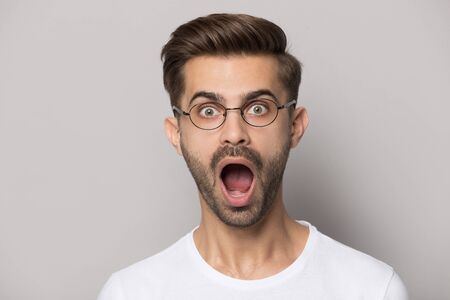 Close up of shocked caucasian young man in glasses isolated on grey studio background look at camera feel stunned, amazed male in spectacles surprised by good promotion, great unexpected news