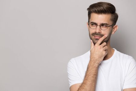 Pensive caucasian young man in glasses wear white t-shirt isolated on grey studio background peek at blank copy space thinking, thoughtful male in spectacles look at offer deal considering option Zdjęcie Seryjne - 131714276