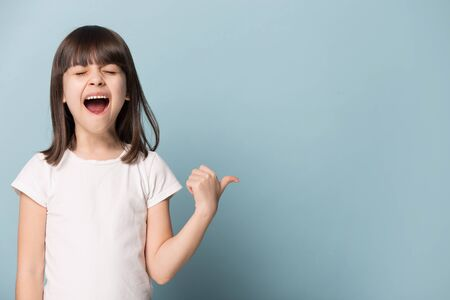 Excited little girl stand isolated on blue studio background point at blank copy space screaming about good sale offer, overjoyed small child show amazing promotion deal, announce kids discount