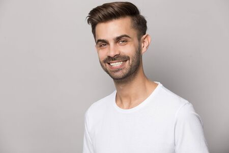 Close up headshot portrait of smiling caucasian young man in white t-shirt isolated on grey studio background look at camera, happy millennial bearded male posing show healthy teeth