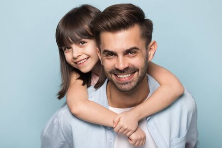 Close up portrait of happy preschool girl piggyback hug young father posing together isolated on blue studio background, smiling little daughter embrace father look at camera, family picture concept