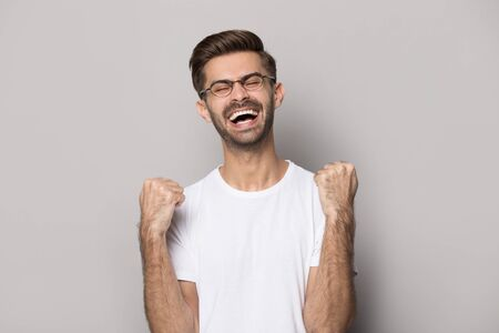Overjoyed caucasian young man in glasses white t-shirt isolated on grey studio background feel euphoric win lottery, excited happy male in spectacles triumph reach success, goal achievement Фото со стока