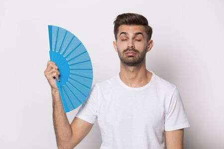 Unhappy caucasian man in white t-shirt isolated on grey studio background use waver feel hot, overheated displeased millennial guy wave cool himself reduce heat with hand fan, no air condition 写真素材
