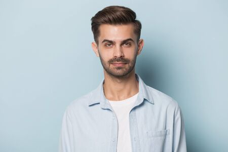 Close up headshot portrait of serious millennial male entrepreneur businessman posing isolated on blue studio background, focused bearded Caucasian man model in shirt casual wear look at camera