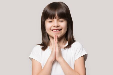Happy cute little girl isolated on grey studio background keep hands in prayer hope believe ask good luck, hopeful smiling small child believer pray do religious superstitious gesture, faith concept