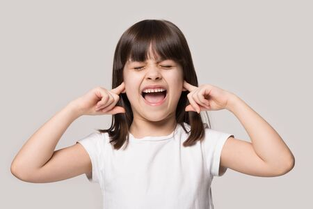 Annoyed little brunette girl isolated on grey studio background close plug ears scream loudly tired by noisy sound, furious angry small child shout yell avoid ignore unbearable loud noise ask quiet
