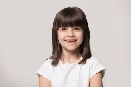 Close up headshot portrait of smiling little girl isolated on grey studio background look at camera, happy small preschooler child in white t-shirt posing feel overjoyed excited show healthy teeth Stockfoto