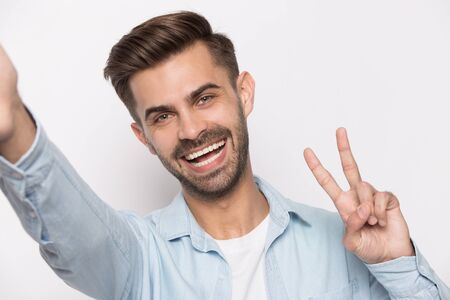 Overjoyed young caucasian man isolated on grey studio background stretch hand making self-portrait picture, smiling happy guy posing show victory sign take selfie on new modern gadget with good camera
