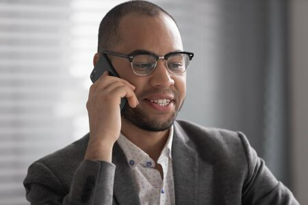 Smiling African American businessman wearing glasses talking on phone close up, manager consulting client customer, speaking by mobile device, employee chatting with friend, pleasant conversation Stok Fotoğraf