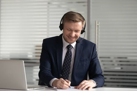 Smiling businessman wearing suit in headset using laptop in office, employee in headphones with microphone watching webinar, making notes, studying online, interpreter translating course