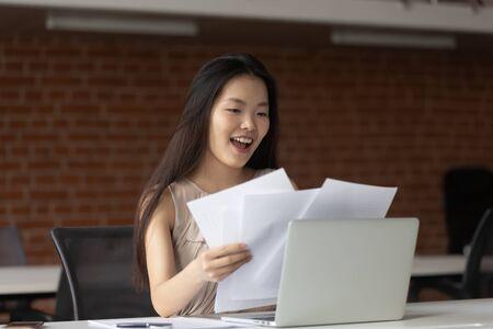 Felice imprenditrice asiatica che legge documenti, buone notizie in lettere cartacee, ottieni un nuovo lavoro o una promozione, grande offerta commerciale, studente entusiasta che riceve risultati positivi degli esami, celebrando il successo