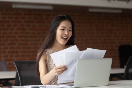 Happy Asian businesswoman reading documents, good news in paper letter, get new job or promotion, great business offer, excited student receiving positive exam results, celebrating success