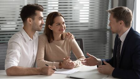 Confident manager, realtor, estate agent consulting young couple about contract terms at meeting in office, happy man and woman taking loan, mortgage or insurance, negotiations concept Фото со стока - 131819569