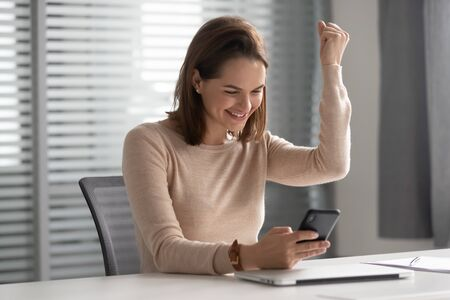 Donna d'affari sorridente felice che utilizza il cellulare, dipendente femminile eccitata che celebra il successo, vince, legge buone notizie nel messaggio e-mail, guarda lo schermo del telefono, risultati positivi degli esami, promozione