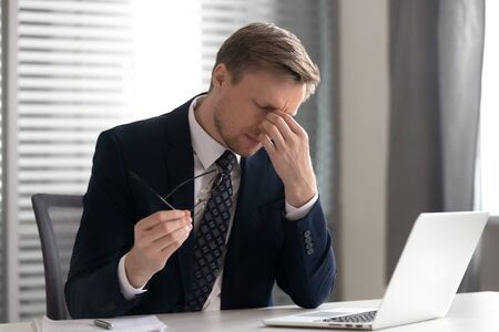 Businessman taking off glasses, suffering from dry eyes syndrome after long laptop use, exhausted employee executive manager ceo feeling eye strain, massaging nose bridge, health problem concept