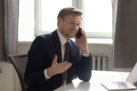 Smiling confident businessman talking on phone, making business call or chatting with friend during break, employee manager consulting client customer by cellphone, pleasant conversation