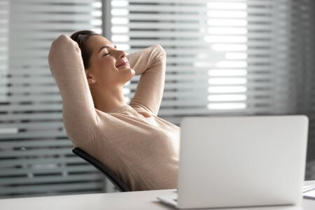 Satisfied businesswoman with hands behind head relaxing in comfortable office chair during break, smiling female employee with closed eyes resting after work done, leaning back, daydreaming