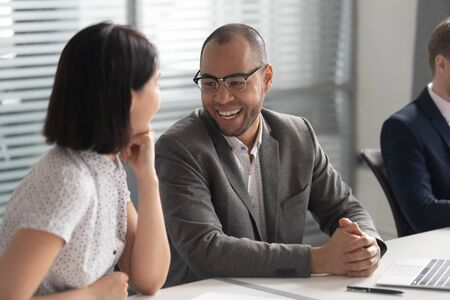 African American businessman wearing glasses talking with businesswoman, diverse colleagues laughing at joke, having fun during break at workplace, discussing new project or sharing ideas