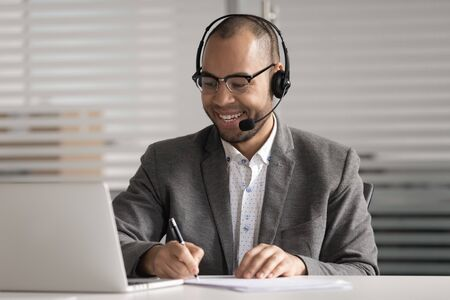 Happy African American employee in headset making notes, using laptop, looking at screen, watching webinar video course, student learning language online, listening lecture, e-learning concept