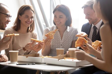 Happy diverse employees enjoying pizza close up, having fun together, office workers team eating Italian fast food, talking laughing at funny joke, good relations, sharing meal at lunch break