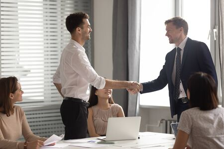 Smiling businessman leader in suit shaking hand of employee at meeting, executive congratulating worker with promotion, thanking for good work results, business partners greeting handshaking