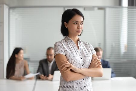 Angry displeased Asian businesswoman with arms crossed standing in office, young female employee has problem at work, feeling tension and pressure, discrimination, bad relations with colleagues 版權商用圖片