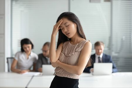 Unhappy Asian businesswoman with closed eyes suffering from headache, touching forehead, feeling pain, health problem concept, female employee intern taking break, relieving pain, self control Stok Fotoğraf