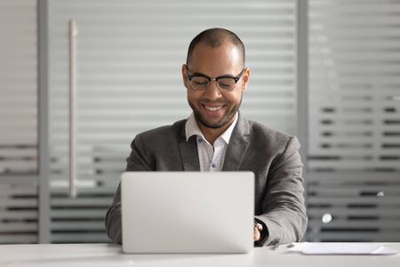 Satisfied African American businessman in glasses using laptop, looking at screen, reading good news in business email, smiling employee working on project, intern chatting in social network Stok Fotoğraf