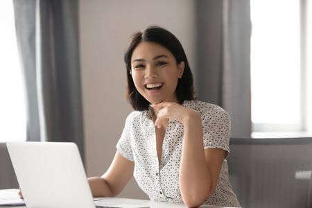 Head shot portrait happy smiling Asian businesswoman at workplace, attractive female employee looking at camera, sitting at desk with laptop, motivated by success, excited student, intern