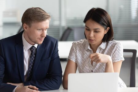 Asian businesswoman and Caucasian businessman working on laptop together, discussing online project, analyzing statistics, writing report, mentor coach helping new employee with corporate software