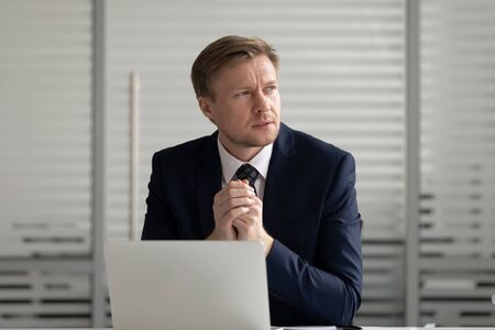 Thoughtful businessman using laptop, pondering online project or startup ideas, business vision, employee working on financial report, sitting at office desk, manager solving business problem