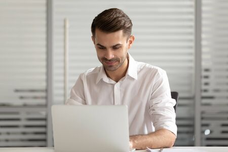 Focused businessman using laptop, looking at computer screen, typing, writing finance report or business email, busy employee working on project, using corporate software, intern chatting online