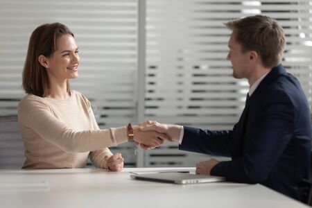 Confident businessman shaking hand of smiling businesswoman in office, good negotiation, recruiter handshaking with smiling female candidate, hiring process, successful job interview concept Stok Fotoğraf