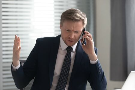 Unhappy angry businessman wearing suit talking on phone, solving corporate business problem, stressed frustrated employee arguing by cellphone, complaining, bad service, receive bad news