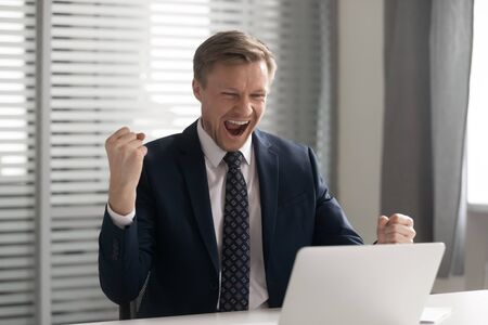 Excited businessman wearing suit celebrating business success, achievement, shouting, employee executive feeling motivated by good work results, get job or promotion, receive great news in email