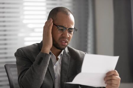 Unhappy African American businessman reading document, business letter, financial report, confused employee receiving unexpected bad news, dismissal notification, money problem, debt Stok Fotoğraf