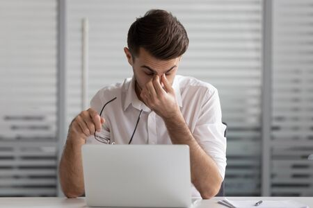 Businessman taking off glasses, suffering from dry eyes syndrome after long laptop use, exhausted employee intern student feeling eye strain, massaging nose bridge, health problem concept