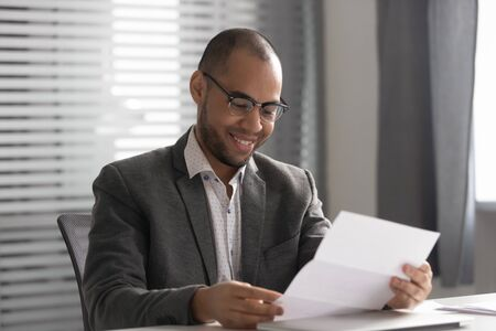 Happy African American businessman in glasses reading document, positive business letter, employee receiving good news, notification, get job or promotion, student satisfied by great exam results Stok Fotoğraf