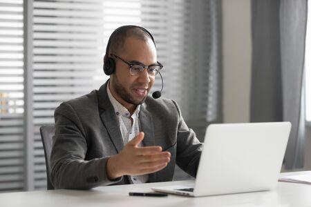 Sorridente dipendente afroamericano in cuffia utilizzando laptop, parlando, agente operatore di call center in cuffia con microfono consulente cliente cliente, studente che impara la lingua online Archivio Fotografico