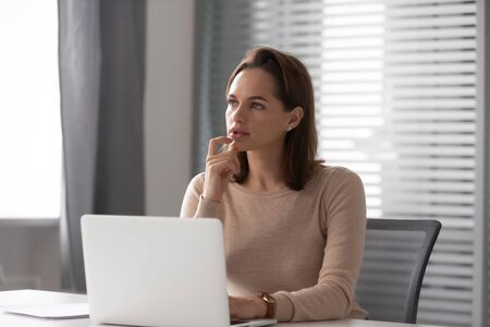 Thoughtful businesswoman using laptop, pondering online project or strategy, business vision, employee working on finance report, sitting at office desk, manager solving business problem